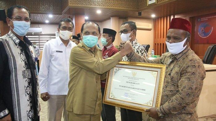 Asisten 1 Pemerintah Aceh, M jafar, menyerahkan penghargaan yang diterima Bupati Pidie Roni Ahmad atau Abusyik, di aula serbaguna Gubernur Aceh, Senin (14/12/2020).