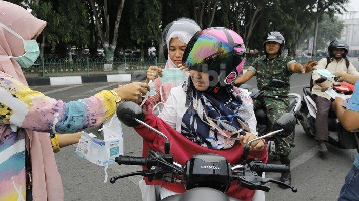 FOTO-FOTO : Peduli Kabut Asap, Suami Istri Bagikan 1.000 Masker di Banda Aceh