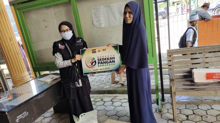 Tim ACT Aceh Maulida menyerahkan paket sembako kepada salah satu warga di Banda Aceh.