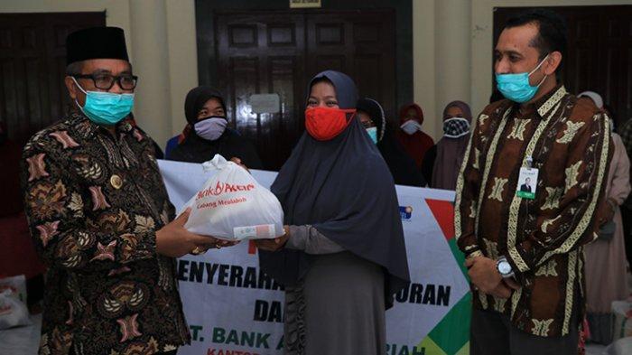 Bupati Aceh Barat, Ramli MS bersama Pemimpin Bank Aceh Syariah Meulaboh, menyerahkan paket sembako kepada penyapu jalan di seputaran kota Meulaboh di Lobi Kantor Bupati Aceh Barat, Kamis (6/5/2021).