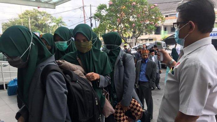 Antrean anggota kafilah Aceh ketika pemeriksaan suhu tubuh saat tiba di pemondokan, Hotel Amaris, Jalan Jenderal Sudirman, Kota Padang berjarak sekitar 23 kilometer dari Bandara Internasional Minangkabau, Kabupaten Padang Pariaman, Jumat (13/11/2020) sore.
