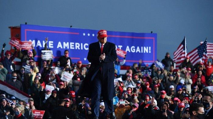 Presiden AS Donald Trump bertepuk tangan saat menggelar kampanye di Bandara Muskegon County, Muskegon, Michigan, AS pada Sabtu (17/10/2020).