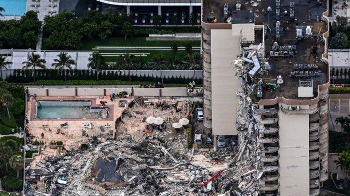 Pemandangan udara ini, menunjukkan personel pencarian dan penyelamatan yang bekerja di lokasi setelah runtuhnya sebagian Menara Champlain South di Surfside, utara Miami Beach, pada 24 Juni 2021. Blok apartemen bertingkat di Florida sebagian runtuh awal 24 Juni, memicu tanggap darurat utama.