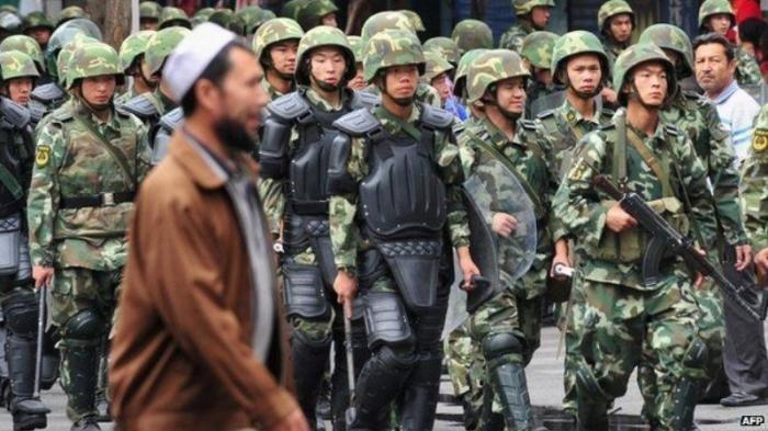 Ilustrasi: Etnis Uighur melintas di depan pasukan keamanan China