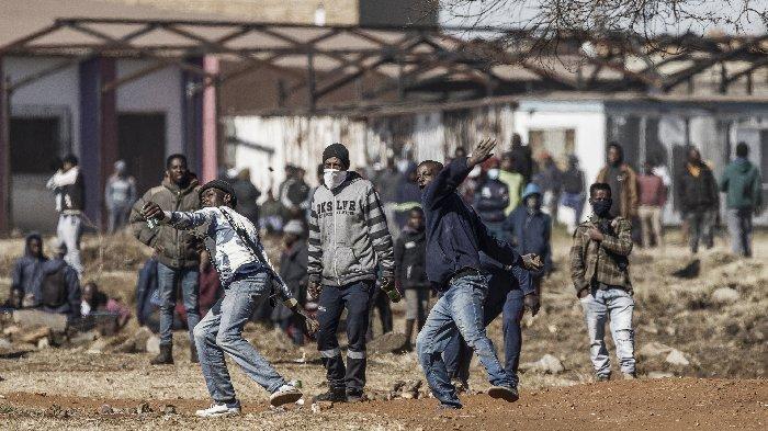Penduduk yang tidak puas melemparkan batu saat mereka menghadapi petugas polisi di pintu masuk mal yang sebagian dijarah di Vosloorus, pada 13 Juli 2021. Toko-toko di dua provinsi Afrika Selatan telah dijarah untuk hari kelima berturut-turut
