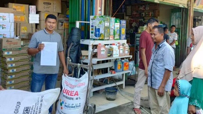 Seorang penyalur pupuk subsidi di Kutablang Bireuen memperlihatkan lampiran e-RDKK kelompok tani kepada petani yang akan menebus pupuk di kiosnya.