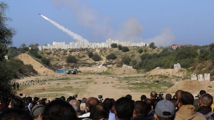 Warga menyaksikan sebuah roket ditembakkan saat latihan militer faksi Hamas di luar Kota Gaza, Palestina, Selasa (29/12/2020).