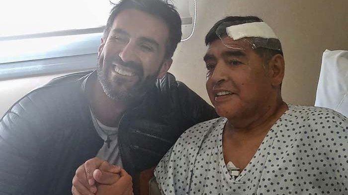 Legenda sepak bola Argentina Diego Maradona (kanan) berjabat tangan dengan dokternya Leopoldo Luque di Olivos, provinsi Buenos Aires, Argentina, Rabu (11/11/2020).