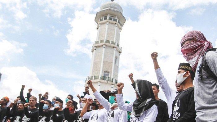 Orang-orang berorasi dengan latar belakang Tugu Modal Indonesia, di depan Masjid Raya Baiturrahman, Banda Aceh, Selasa (8/12/2020). Kawasan ini sering menjadi lokasi aksi warga Aceh untuk menyampaikan aspirasi.