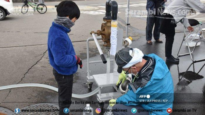 FOTO - Kondisi Terkini Fukushima Jepang, Setelah Diguncang Gempa Berkekuatan 7.1 Magnitudo - mengambil-air-minum.jpg