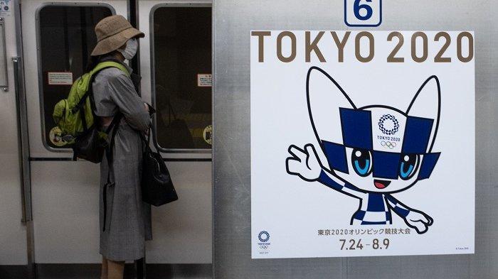 Seorang calon penumpang yang memakai masker berdiri dekat poster maskot Olimpiade Tokyo 2020 di Miraitowa, Tokyo, Jepang, Senin (20/4/2020).