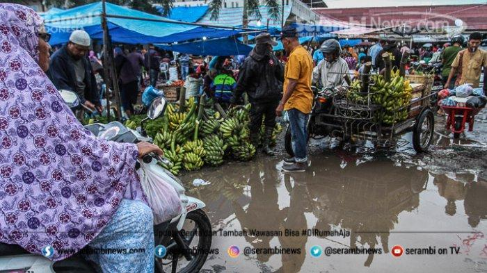 FOTO - Wajah Pasar Induk Lambaro Ketika Musim Hujan, Pedagang Berjualan Diantara Kubangan Lumpur - pembeli-melintasi-jalan-becek-di-pasar-induk-lambaro.jpg