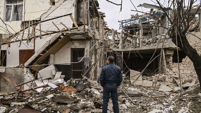 Seorang petugas polisi berdiri di depan rumah yang hancur terkena serangan rudal jet tempur Azerbaijan di Ibu Kota Stepanakert, Nagorno-Karabakh, Rabu (7/10/2020).