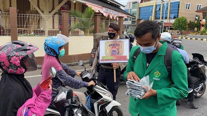 Tingkatkan Protkes, Polisi dan Mahasiswa Unimal Bagikan Masker di Simpang Jam