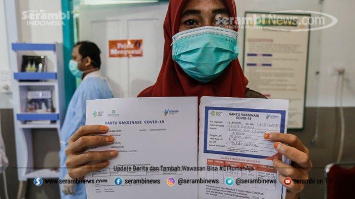 Petugas kesehatan memperlihatkan kartu vaksinasi COVID-19 Sinovac di Rumah Sakit Meraxa, Banda Aceh, Aceh, Selasa (9/2/2021).