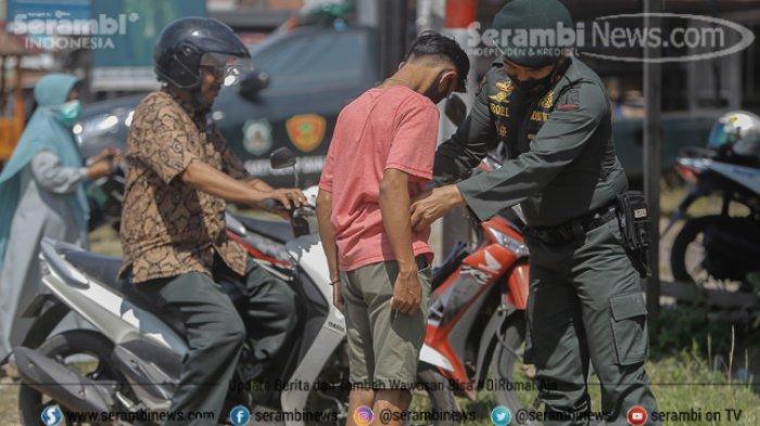 Polisi Wilayathul Hisbah (WH) memeriksa seorang lelaki yang mengunakan celana pendek saat razia busana muslim di kawasan, Lampeuneurut, Aceh Besar, Kamis (18/2/2021).