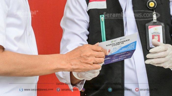 Presiden Joko Widodo menerima Kartu Vaksinasi Covid-19 setelah disuntik di Istana Merdeka, Jakarta, Rabu (13/1/2021).
