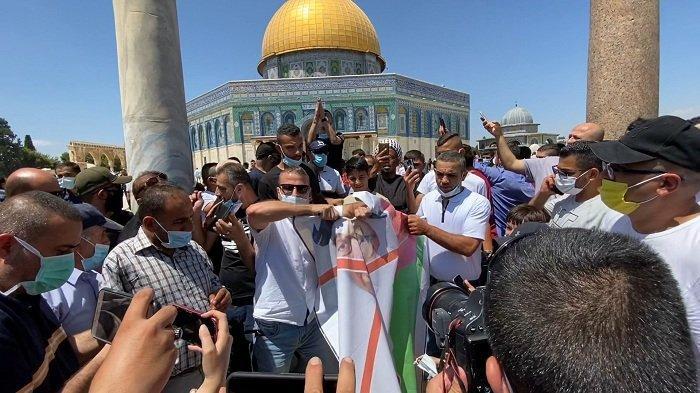 Demonstran Palestina merobek potret Putra Mahkota Abu Dhabi, Sheikh Mohammed bin Zayed al-Nahyan untuk memprotes pembukaan hubungan UEA dengan Yahudi di Kompleks Masjid al-Aqsa, Jerusalem, Jumat (14/8/2020).