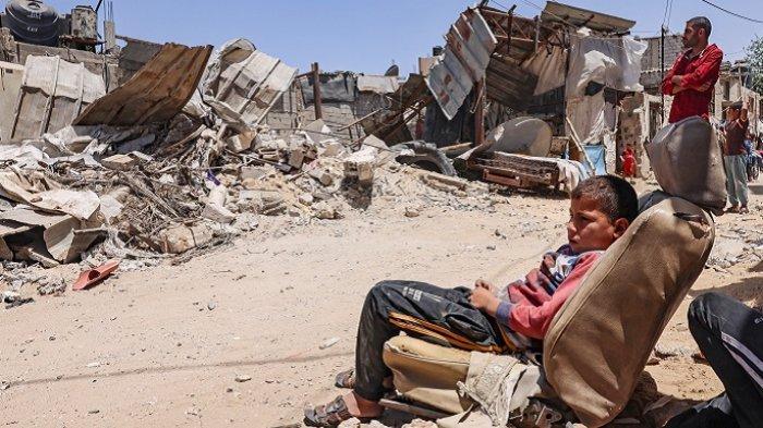 Warga Palestina melihat rumah mereka yang hancur terkena serangan udara Israel, di Kota Rafah, Jalur Gaza selatan, Palestina, Minggu (16/5/2021)