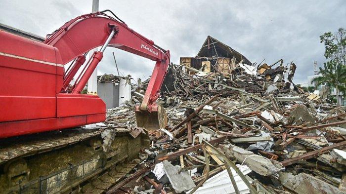 FOTO - Kondisi Kerusakan Akibat Gempa 6,2 SR di Sulawesi, Korban Meninggal Mencapai 56 Orang - sebuah-ekskavator-membersihkan-lokasi-gedung.jpg