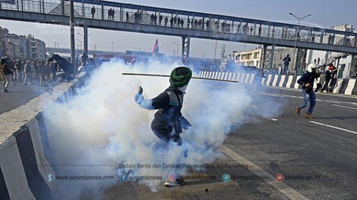 FOTO -  Ribuan Petani India Gelar Demonstrasi Pada Peringatan Hari Republik - seorang-petani-melemparkan-kembali-selongsong-gas-air-mata.jpg