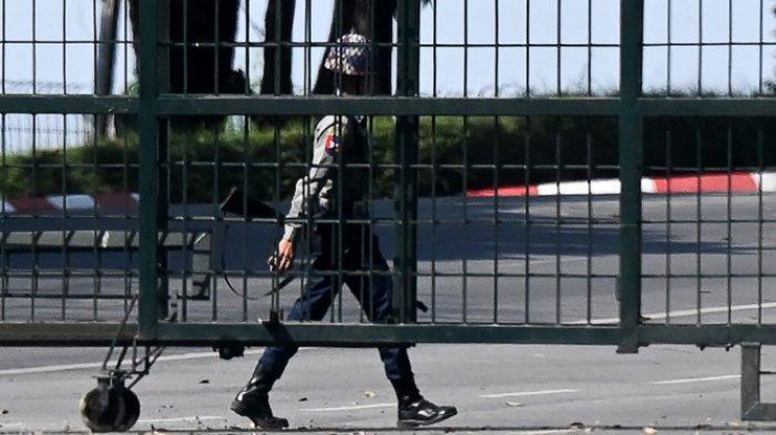 Seorang polisi berjalan di belakang area yang diblokir oleh gerbang dekat bandara internasional di Yangon pada 1 Februari 2021