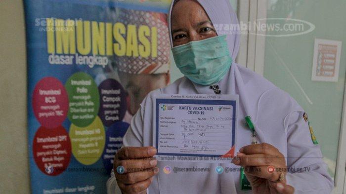 FOTO - Penyuntikan Perdana Vaksin Sinovac Covid-19 Bagi Tenaga Medis dan Unsur Muspika Aceh Besar - seorang-tenaga-kesehatan-menunjukan-kartu-vaksinasi-covid-19.jpg