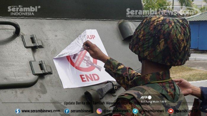 FOTO - Polisi Myanmar Pakai Ketapel Untuk Halau Massa, Militer Ancam 20 Tahun Penjara Bagi Pendemo - seorang-tentara-menghapus-tanda-protes.jpg