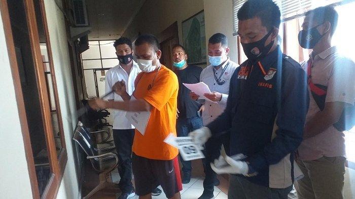 Tersangka Hen sedang melakukan rekontruksi kasus pencurian di Bappeda Bireuen, Kamis (08/04/2021).