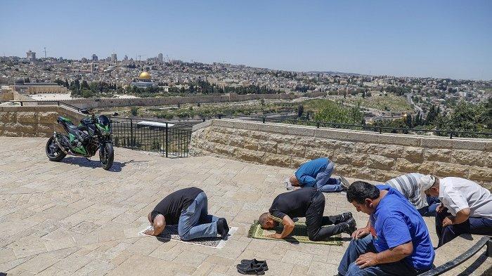 Warga Palestina melaksanakan shalat Jumat (1/5) dalam jumlah sedikit di depan Bukit Zaitun dengan latar belakang kota tua Jerusalem dan Masjid Al-Aqsa yang ditutup, Jumat (1/5/2020).