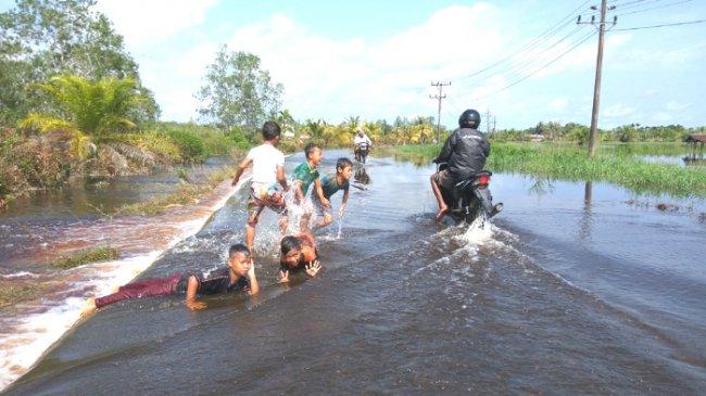 anak-anak-korban-banjir-bermain-di-badan-jalan-yang-terendam_20170109_090920.jpg