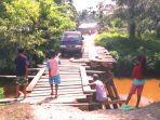 anak-anak-memperhatikan-satu-unit-mobil-saat-melintasi-jembatan.jpg