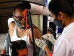 petugas-swab-virus-corona-terhadap-seorang-pria-india.jpg