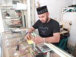 saiful-bahri-mori-penjual-emas-di-toko-london-lhokseumawe-melayani-pembeli-selasa-892021.jpg