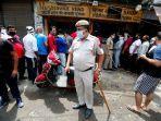 seorang-polisi-india-berdiri-di-depan-toko-minuman-keras-di-new-delhi.jpg