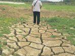 seorang-warga-berjalan-di-atas-permukaan-tanah-waduk-paya_20180403_095059.jpg