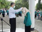 wakil-rektor-i-usk-prof-marwan-memasangkan-tanda-peserta.jpg