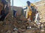 warga-berada-di-antara-puing-puing-rumah-yang-runtuh-setelah-gempa-bumi-di-barat-daya-pakistan.jpg
