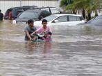 warga-mendorong-motornya-ketika-melintasi-banjir-yang-merendam-jalan-caman.jpg