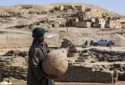 Foto tertanggal 10 April 2021 memperlihatkan seorang pekerja mmebawa sebuah pot yang ditemukan di kota emas Firaun Mesir. Kota berjuluk The Rise of Aten ini berdiri saat masa pemerintahan Amenhotep III dan hilang 3.000 tahun lalu.