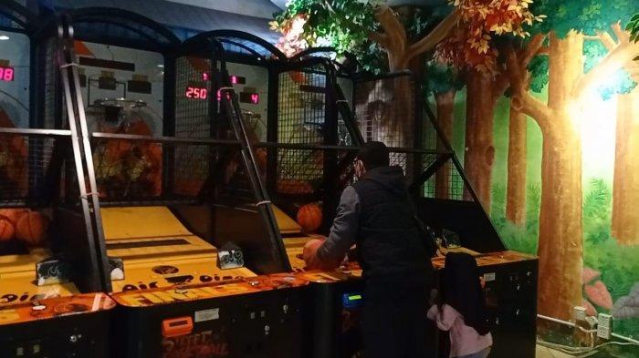AMBON: Ayah dan anaknya sedang seru memainkan wahana basket, Kamis (27/5/2021) malam.