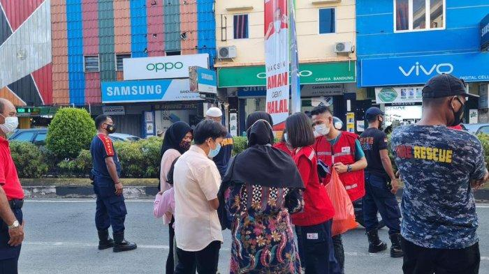 AMBON: Palang Merah Indonesia (PMI) Ambon bersama Dinas Pemadam Kebakaran Kota Ambon membagikan takjil gratis kepada warga yang melintas di kawasan Jalan A.Y. Patty, Jumat (30/4/2021). (Dok TribunAmbon.com/Ridwan)