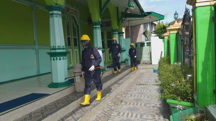 AMBON - Menggunakan APD lenngkap KBR Brimob Polda Maluku lakukan penyemprotan cairan disenfektan pada Masjid Kota Ambon Jumat, (5/2/2021).