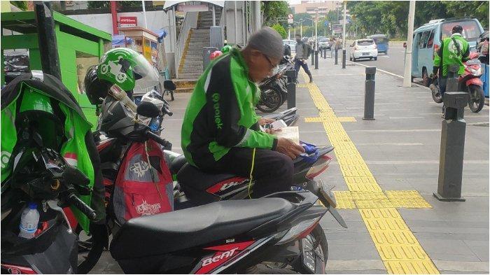 Viral Driver Ojol Baca Alquran di Atas Sepeda Motor saat Menunggu Orderan
