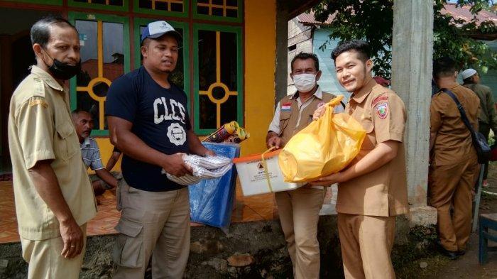 Petugas BPBD Maluku Tengah saat menyerahkan bantuan logistik kepada Fadli Marasabessy di Kompleks Pahlawan, Namaelo, Kota Masohi. Senin (12/7/2021).