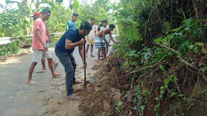 Warga gotong royong membersihkan material longsor dari talud di Kampung Ahuru ThR 2 , Kecamatan Sirimau, Kota Ambon, Kamis (12/8/2021).