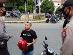 seorang-pengendara-yang-tidak-menggunakan-masker-tengah-ditindak-aparat-kepolisian.jpg