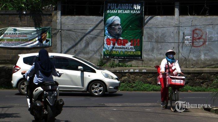 Pengendara melewati baliho Habib Rizieq dengan ukuran cukup besar yang ditempel pada tembok sebuah pabrik di Jalan Cibaligo, Kota Cimahi, Jawa Barat, Jumat (06/11/2020).