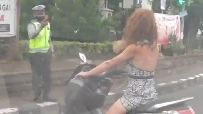 Istimewa Aksi konyol sang pengendara motor yang dikendarai seorang wanita asing (bule) di Simpang Teuku Umar - Imam Bonjol, Denpasar, Bali yang terekam kamera handphone milik warga. Terlihat juga sang bule yang akhirnya diberikan surat tilang.