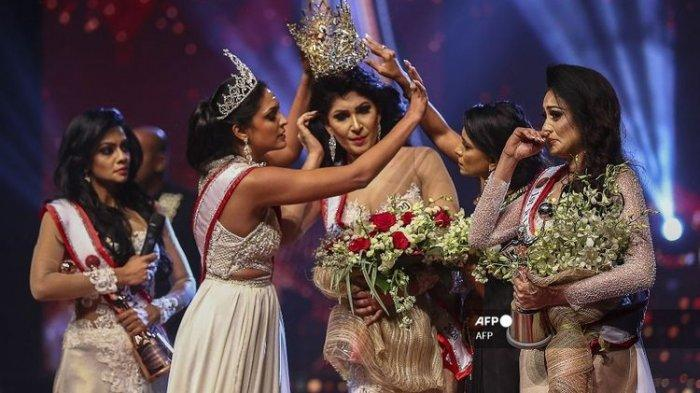 Dalam foto yang diambil pada 4 April 2021, pemenang Mrs World 2020 Caroline Jurie (dua dari kiri) mencopot mahkota dari juara Mrs Sri Lanka 2021 Pushpika De Silva karena dituduh sudah bercerai.